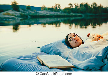 Pretty woman is laying on the floating bed with a book and toy.