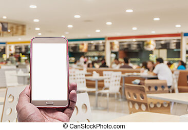 Hand with smartphone on blurred in food court background,...