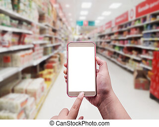 Hand with smartphone on blurred in department store...