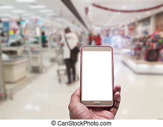 Hand with smartphone on blurred in shopping mall background...