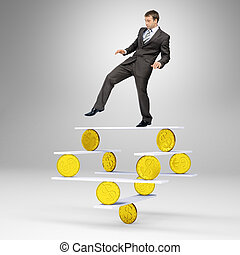 Businessman standing on balance with gold coins and looking...
