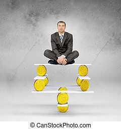 Businessman sitting on balance with gold coins and looking...