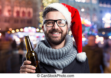Young man with beer bottle - Young man with Santa hat and...