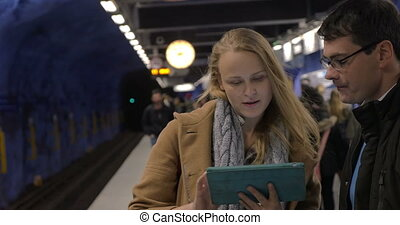 Modern urban people with pad in subway - Young man and woman...
