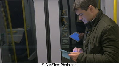 Commuter with pad in underground train - Young man using...
