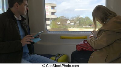 Two passengers in train using pad and smart watch - Male and...