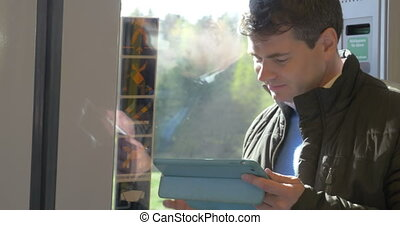 Caucasian man using touch pad on the train