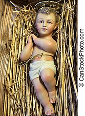 ancient statue of baby jesus newborn resting in the manger at Christmas