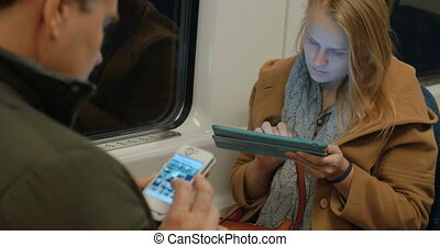 Woman in Metro Train Typing in Tablet - Young woman is...