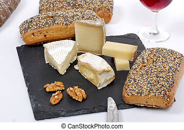 French cheeses on slate with bread and nuts - Various French...