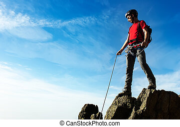 A climber helps his partner to reach the summit of a mountain pe