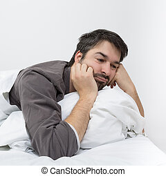 sleeping pills - man with beard lying in a bed with white...