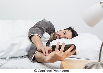 woken up by calling - man with beard lying in a bed with...