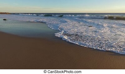 Waves gently wash up onto the beach, then recede as the sun...