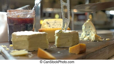 Hands Cutting Soft Cheese with Knife - Closeup shot of a...