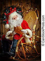 christmastime - Santa Claus sitting at his wooden house in a...