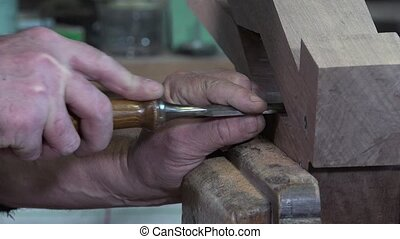 carpenter working in his workshop - finishing cuts with a...