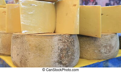 Wheels of cheese at a market - Cheese wheels stacked on the...