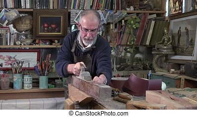 carpenter working in his workshop - planing a piece of wood