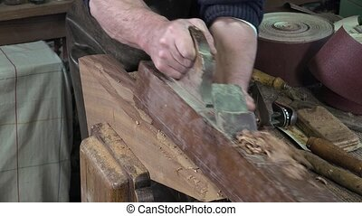 carpenter working in his workshop - planing a piece of wood...