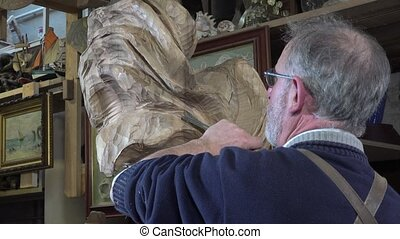 carpenter working in his workshop - sculpture with a wood...