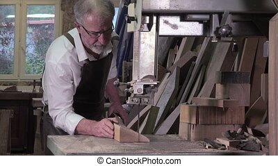 carpenter working in his workshop - cutting using a bandsaw