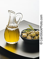 Olive oil and olives on a black plate