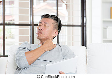 Mature Asian man shoulder pain while using tablet computer -...