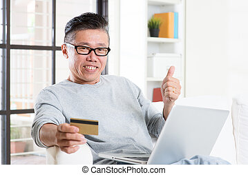 Asian man making online payment and thumb up