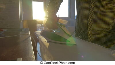 Man ironing shirt in sunny room - Close-up shot of a man...