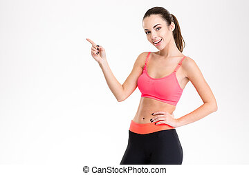 Cheerful attractive young fitness woman pointing away