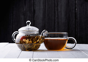 Glass teapot with blooming green tea and cup