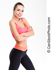 Cute lovely young fitness woman posing with folded hands