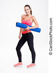 Attractive smiling young fitness woman holding yoga mat -...