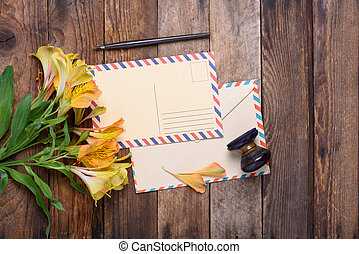 Retro postcard with envelope, stamp and flowers on vintage...