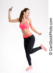 Fitness woman listening to music from mobile phone and dancing