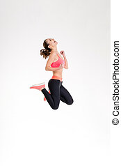 Attractive excited fitness girl in sportwear jumping of joy...