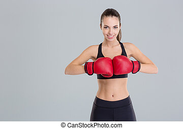 Beautiful smiling young fitness woman wears red boxing...