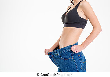 Young sportswoman with beautiful body in old big jeans