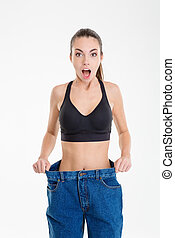 Shocked slim fitness girl in jeans that became too big