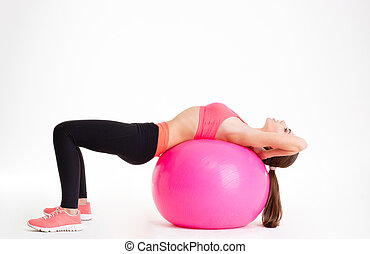 Concentrated beautiful fitness girl in sportwear exercising...