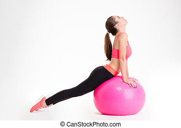 Concentrated beautiful fitness girl doing sport with fitball