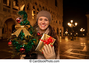Woman with Christmas tree and gift box on Piazza San Marco -...