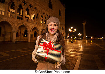 Woman showing Christmas gift box on Piazza San Marco, Venice...