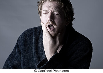 Man in Pain holding his Jaw Toothache - Dramatic Shot of a...