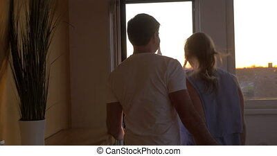 Man and woman looking at the city from balcony