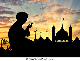 Silhouette of man praying - Concept of the Islamic religion....