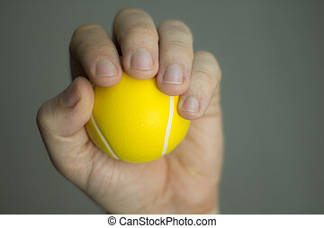 Physiotherapy exercise ball - Man hand squeezing an exercise...