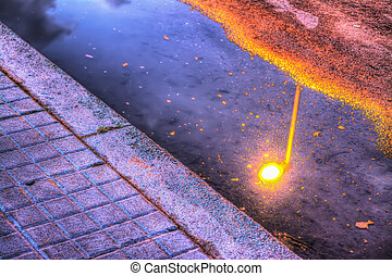 lamppost refelcted in a puddle at sunset - bright lamppost...