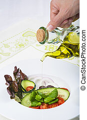 Dressing a gourmet salad with olive oil - Pouring virgin...